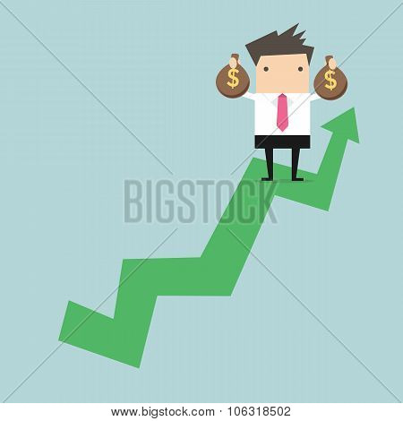 Businessman holding money bag on growing graph