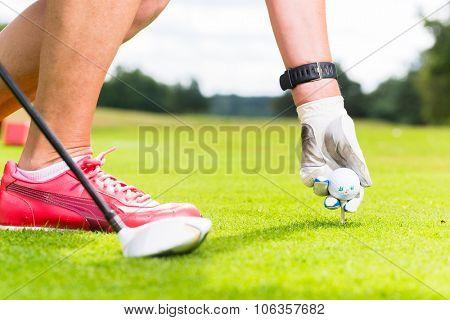 woman putting golf ball on tee, close shot