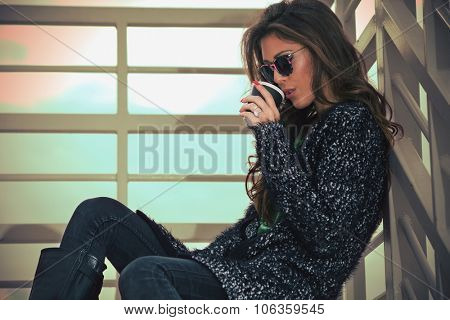 young woman in cardigan and sunglasses drink coffee from paper cup on stairs, autumn day outdoor
