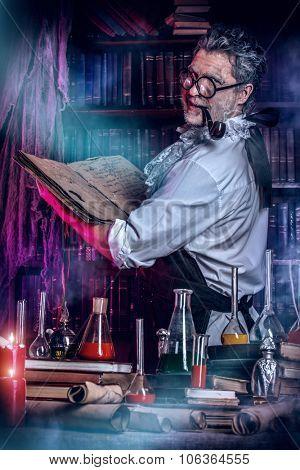 The old man medieval scientist working in his laboratory. Alchemist. Halloween.