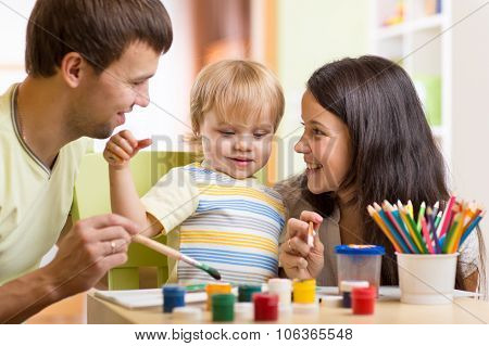 kid painting together with parents ay home