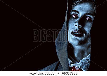 Gloomy, scary vampire in a black cloak hiding his face under a hood. Halloween.