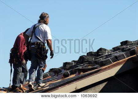 Two Workmen Walking On Roof Of Building