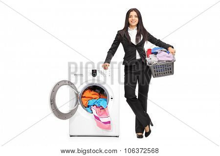 Full length portrait of a businesswoman standing by a washing machine and holding a laundry basket full of clothes isolated on white background