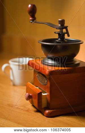 Old coffee grinder and cup on a table and textured wood background poster