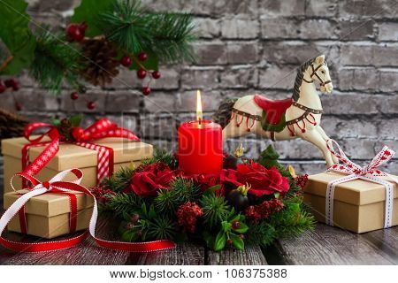 Christmas decorations with red candle,gift boxes and rocking horse on  the old wooden table