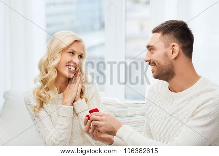 love, couple, relationship, proposal and holidays concept - happy man giving engagement ring in little red gift box to woman at home poster