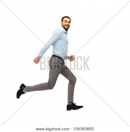 business, freedom, movement and people concept - smiling young man jumping or running away