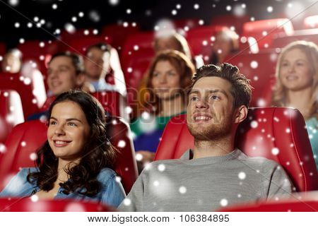 cinema, entertainment and people concept - happy friends or couple watching movie in theater over snowflakes