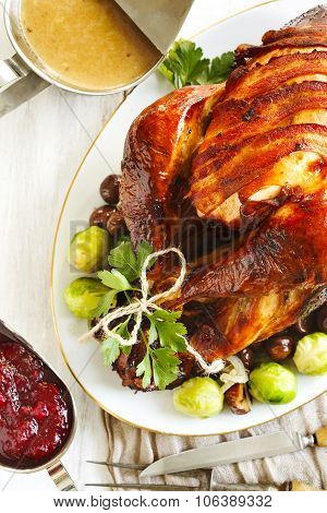 Roasted Turkey With Bacon And Garnished With Chestnuts And Brussels Sprouts.