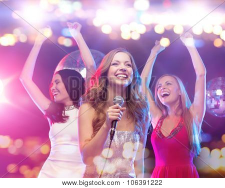 party, holidays, nightlife, entertainment and people concept - concept - happy women with microphone singing karaoke and dancing at night club