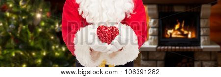 christmas, holidays, love, charity and people concept - close up of santa claus with heart shape decoration over living room with fireplace and christmas tree background