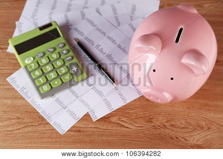 Pig moneybox and calculating equipment on desk closeup poster