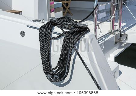 Close-up Of A Mooring Rope With A Knotted End Tied Around A Cleat On A Wooden Pier. Nautical Mooring