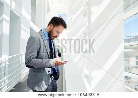 Young smart male entrepreneur reading something on cell telephone during break