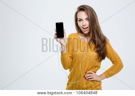 Portrait of a cheerful woman showing blank smartphone screen isolated on a white background