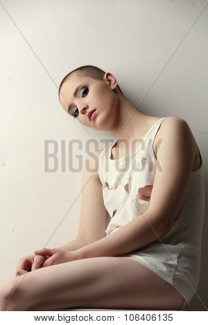 Shot of pretty skinhead girl in ragged t-shirt