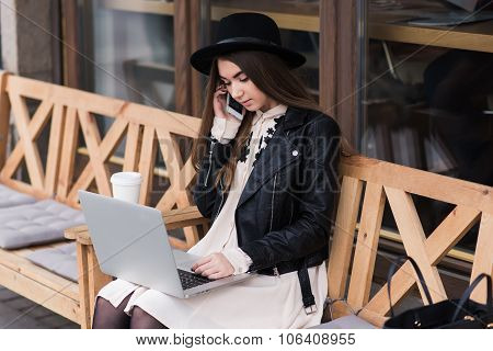 Stylish woman with trendy look talking on cell telephone during work on portable laptop computer