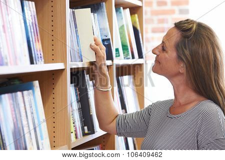 Woman Choosing A Book In Bookstore