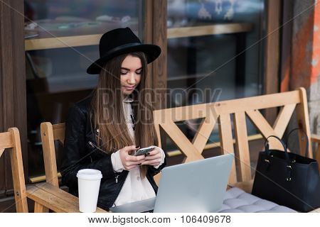 Young hipster girl using  mobile phone while relaxing after walking