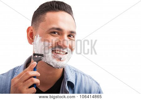 Portrait of a handsome man with shaving cream on his face and using a razor to shave poster