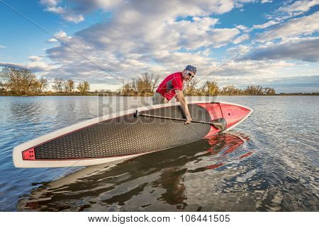senior male launching  his 14 feet long expedition stand up paddleboard on a lake in Colorado, fall scenery