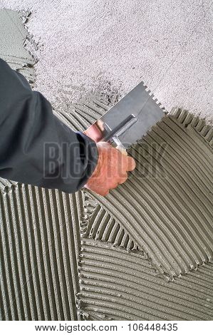 Construction Notched Trowel With Grey Cement Mortar For Tiles Work