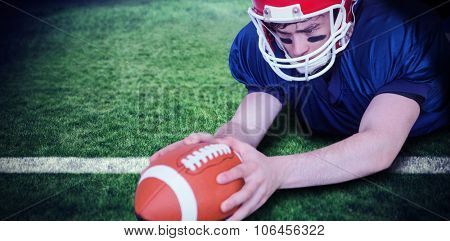 American football player scoring a touchdown against rugby pitch