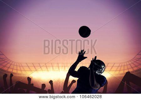 American football player catching ball against football stadium with cheering crowd