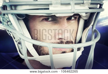 Close-up portrait of stern American football player against american football arena