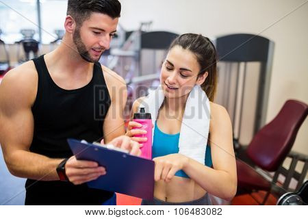 Trainer explaining workout regime to woman at the gym