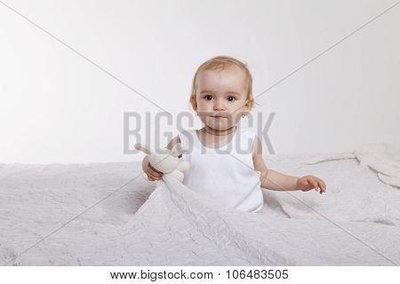 Toddler girl sitting on the bed rug dreaming and holding her plushy pet poster