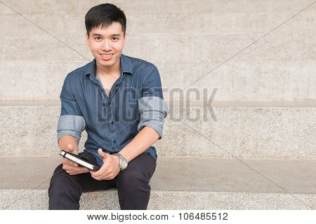Young male student reads a book in university in the afternoon in campus