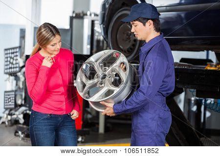 Male technician showing metallic hubcap to female customer at garage