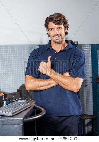 Portrait of happy male mechanic gesturing thumbsup while standing at auto repair shop