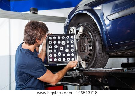 Male mechanic adjusting wheel alignment machine on car in garage