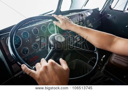 Cropped image of fireman's hands holding steering wheel of firetruck at station poster