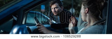 Panorama of aggressive car robber and helpless female victim poster