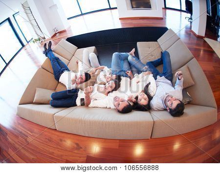 portrait of happy young group of friends get releax and have fun at modern home interior, top view