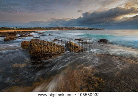 Sunrise seascape flowing water over the rocks