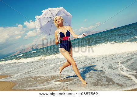 Attractive blond woman running in the sea