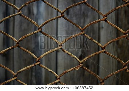 Wire Link Fence On Wooden Background