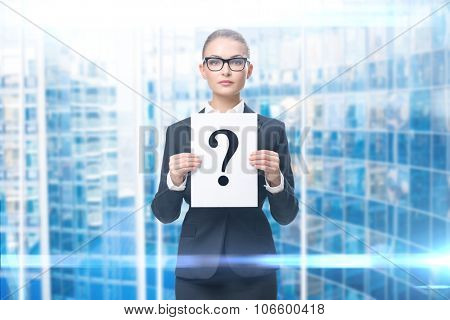Portrait of businesswoman handing question mark, blue background. Concept of problem and solution