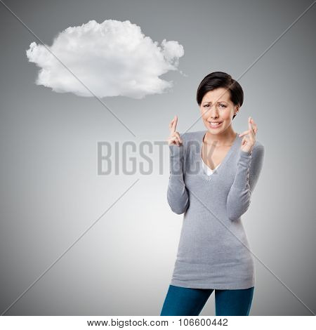 Worrid woman shows crossed fingers to cloud, isolated on grey