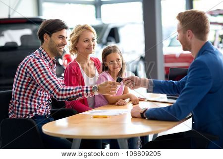 car dealer selling new car to young family with child girl