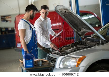 Mechanic inspection with manager on car damage