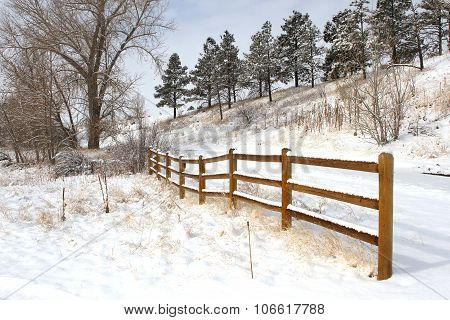 A split rail fence follows a snowy trail on a winters day poster