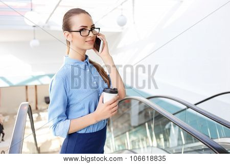 Female office worker is speaking on the phone.