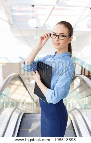 Office employee with clipboard fixes her glasses.