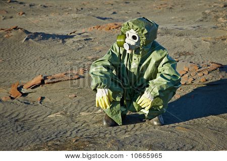Scientist In Protective Suit And Gas Mask Sitting On Slag